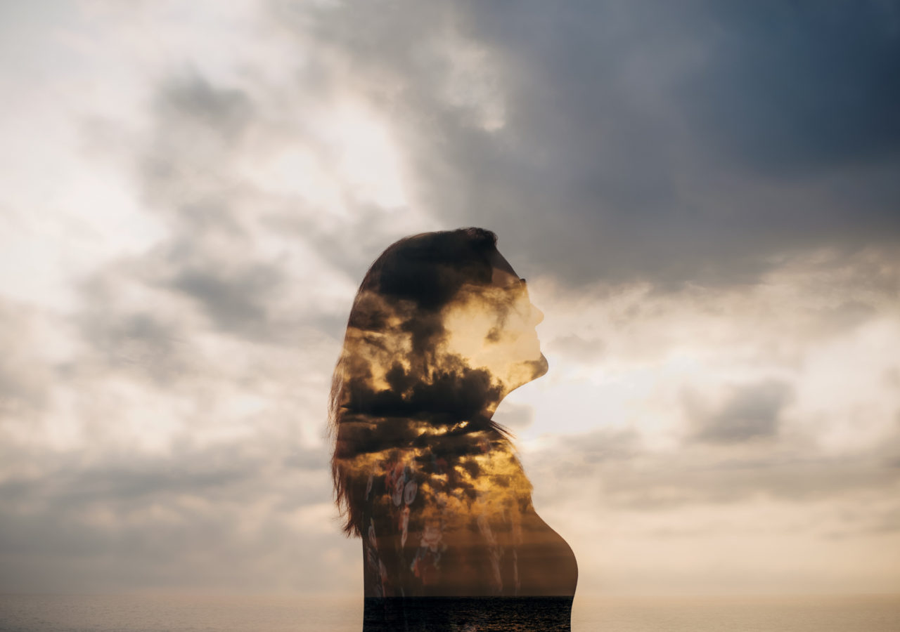 double exposure photo of a photographer silhouette against a sunset sky self portrait