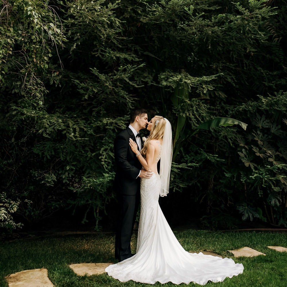 a romantic photo of a bride & groom almost kissing in a lush green garden after their wedding ceremony at the Hartley Botanica near Moorpark