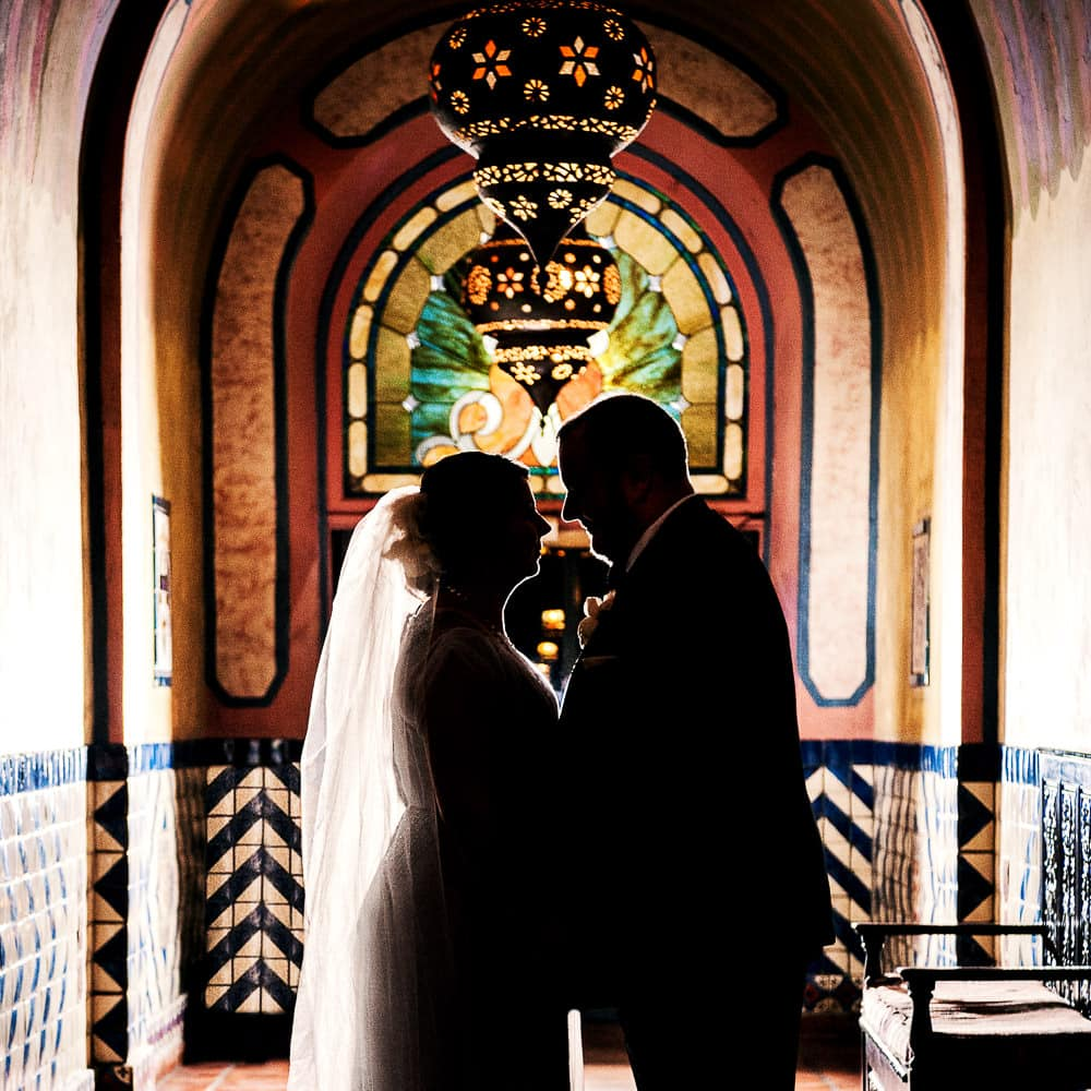 a colorful & dramatic silhouette of a bride & groom standing in a vintage hallway at the Hotel Figueroa in Downtown Los Angeles