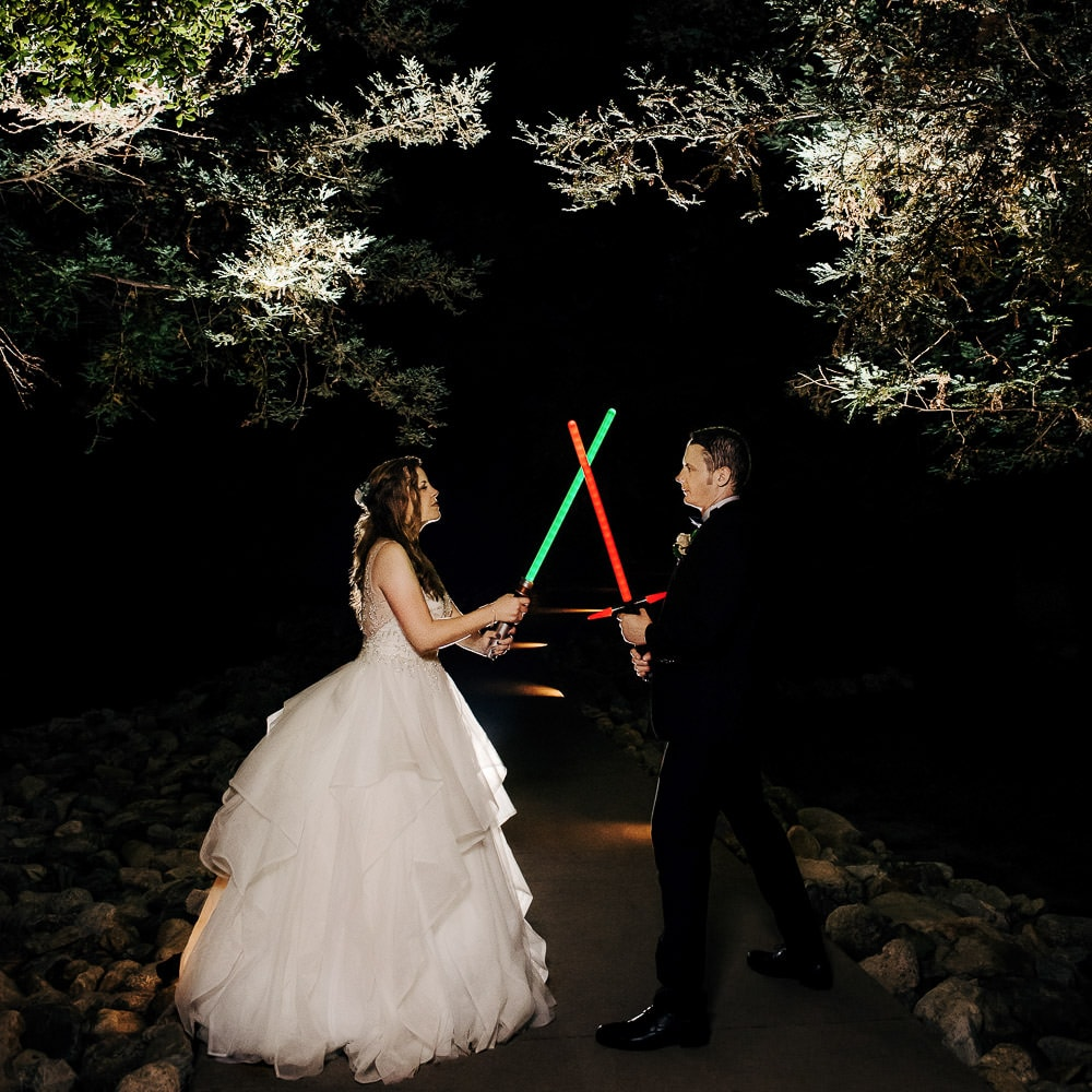 a cool unique night portrait of a bride & groom holding lightsabers during a Star Wars themed wedding at Middle Ranch in Lake View Terrace Sylmar