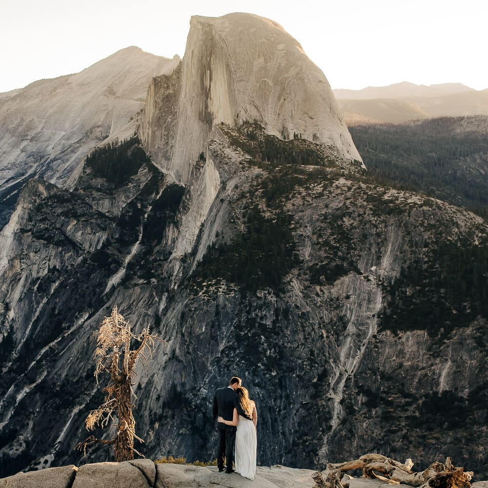a beautiful photo of a bride & groom standing in front of Half Dome at Glacier Point in Yosemite during sunrise at dawn