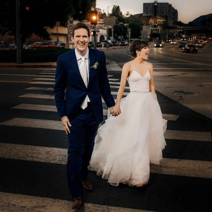 a fun & candid photo a couple walking down the street Cahuenga in Hollywood on their wedding day