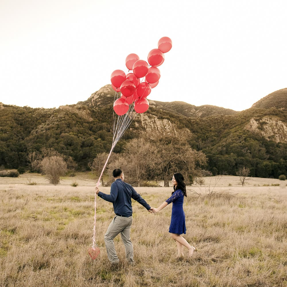 a whimsical photo of a couple in dress clothes walking through a field with red balloons with mountains in the background at Malibu Creek State Park