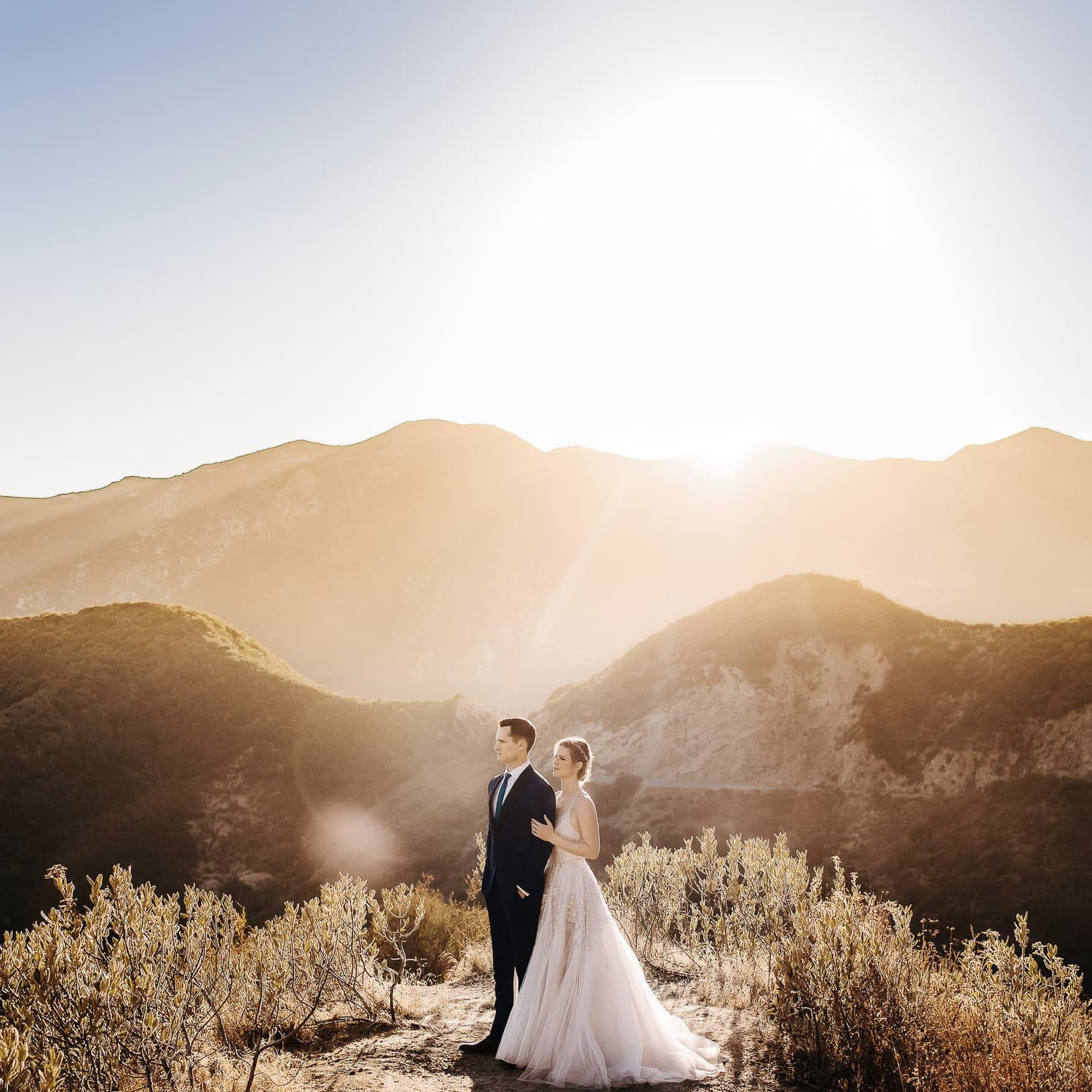 a dramatic editorial portrait of a bride & groom standing together and facing outwards on top of a mountain in the Angeles National Forest