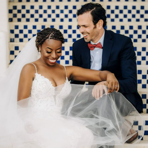 a cute photo of a bride & groom sitting and laughing together on vintage blue steps during their Jewish & Nigerian wedding at King Gillette Ranch in Malibu