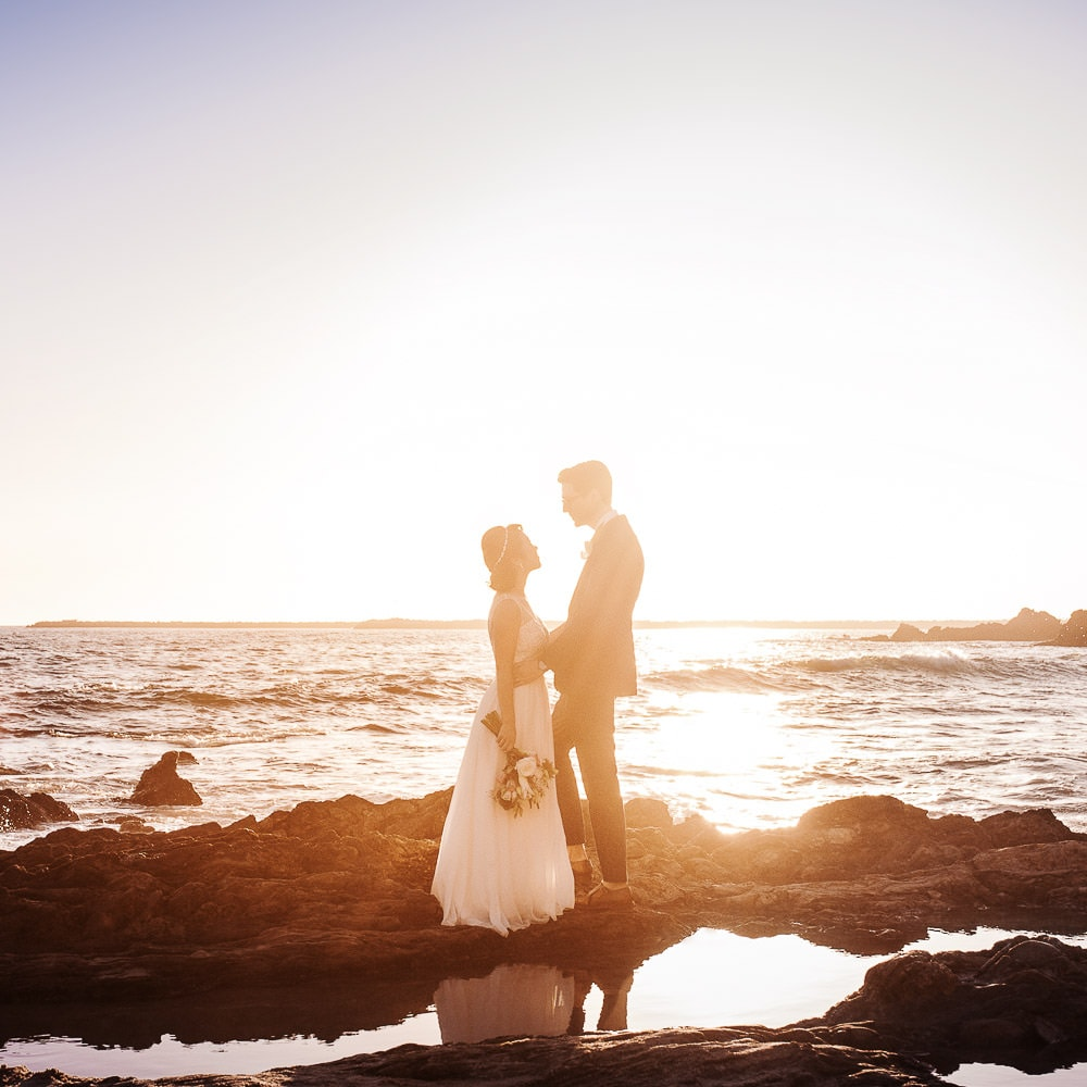 a colorful still portrait of a bride & groom standing on rocks & facing each other during sunset on a beach in Newport on the day of their Laguna Beach wedding