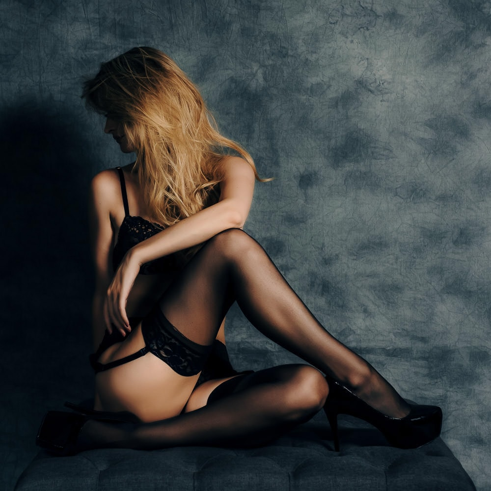 a sensual studio boudoir portrait of a woman in black lingerie sitting on an ottoman and turned away from the camera