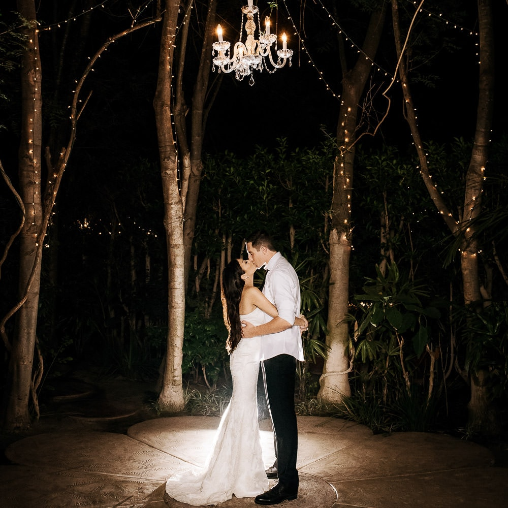 a romantic storybook photo of a bride & groom kissing underneath a chandelier at their ceremony site at night