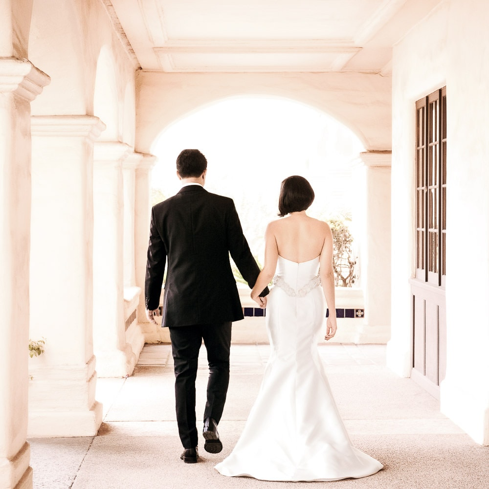 a soft photo of a bride & groom walking away from the camera under Spanish architecture during their wedding in Camarillo