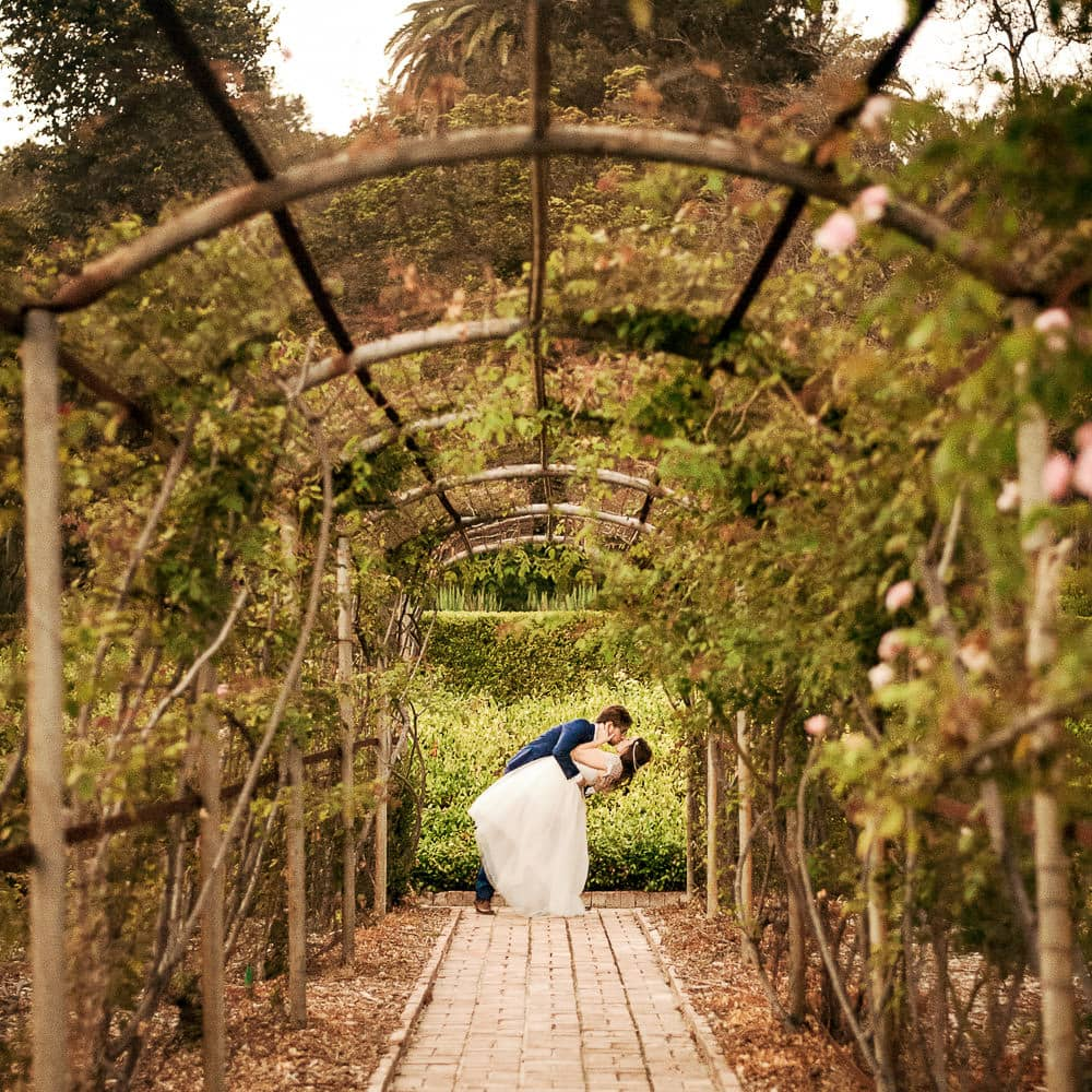 a whimsical storybook photo of a bride & groom in a dip kiss in a green garden during their wedding at Wattles Mansion in Hollywood
