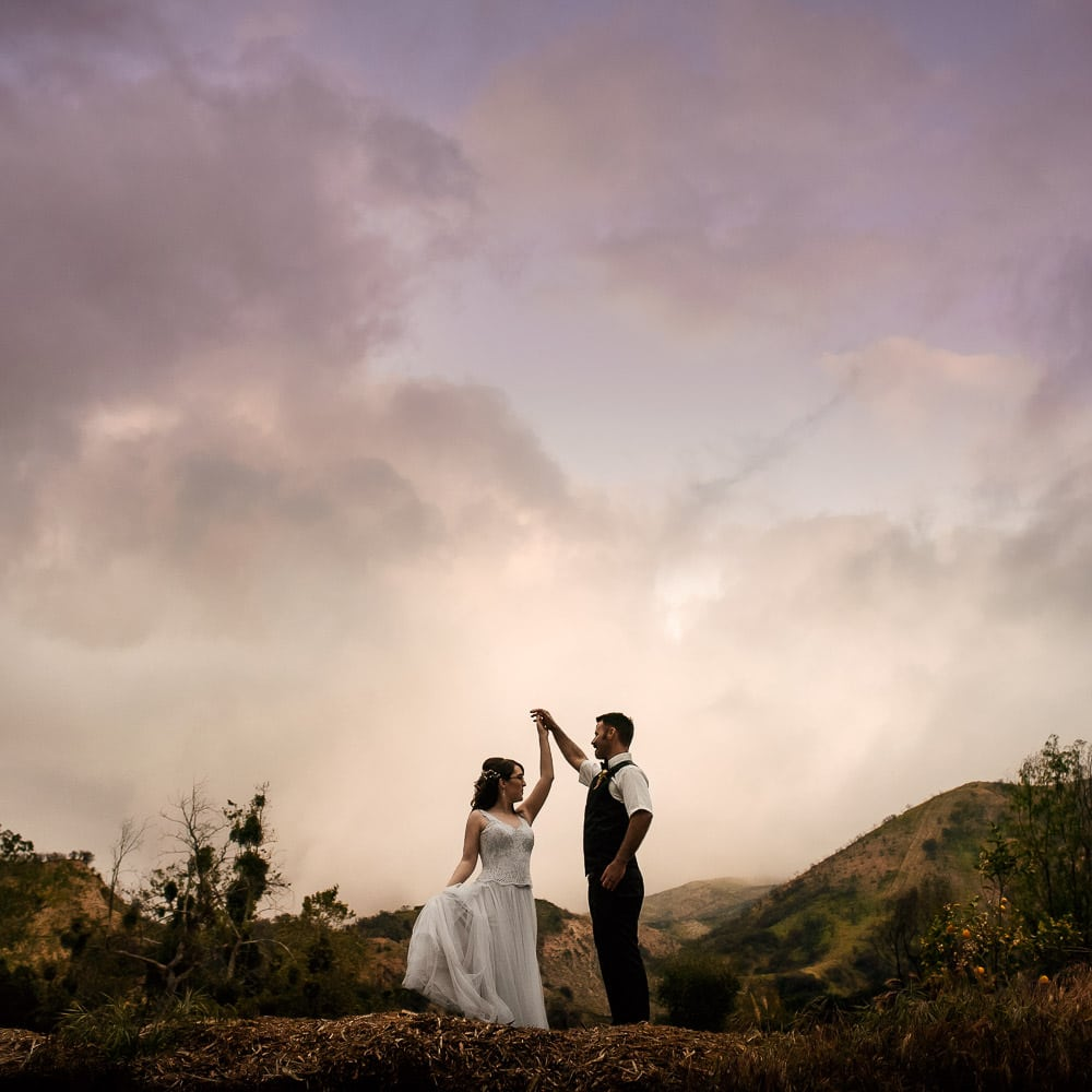 a dramatic & colorful silhouette portrait of a bride & groom dancing on top of a mountain at Reptacular Ranch in Sylmar during sunset